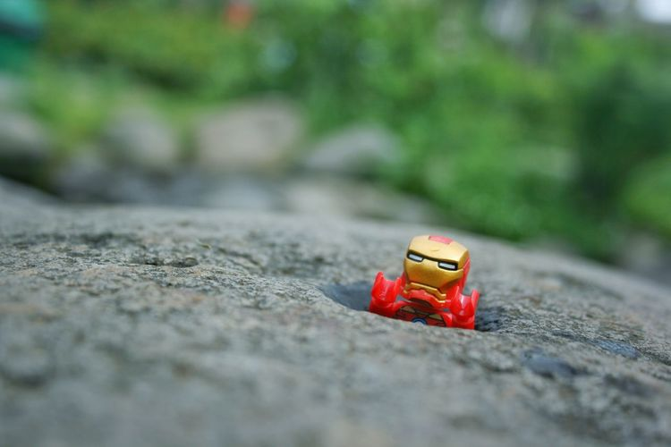 Close-up of red toy car on rock