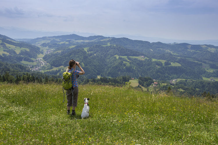 Woman and dog hiking on Hörnli, Zürich Adventures Hiking Adult Adventure Beauty In Nature Binaculars Day Dog Domestic Animals Field Friendship Full Length Grass Landscape Mountain Mountain Range Nature One Animal One Person Outdoors Overlooking People Pets Real People Sky Solotraveler Switzerland Women Young Adult