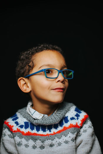 Portrait of boy wearing sunglasses against black background