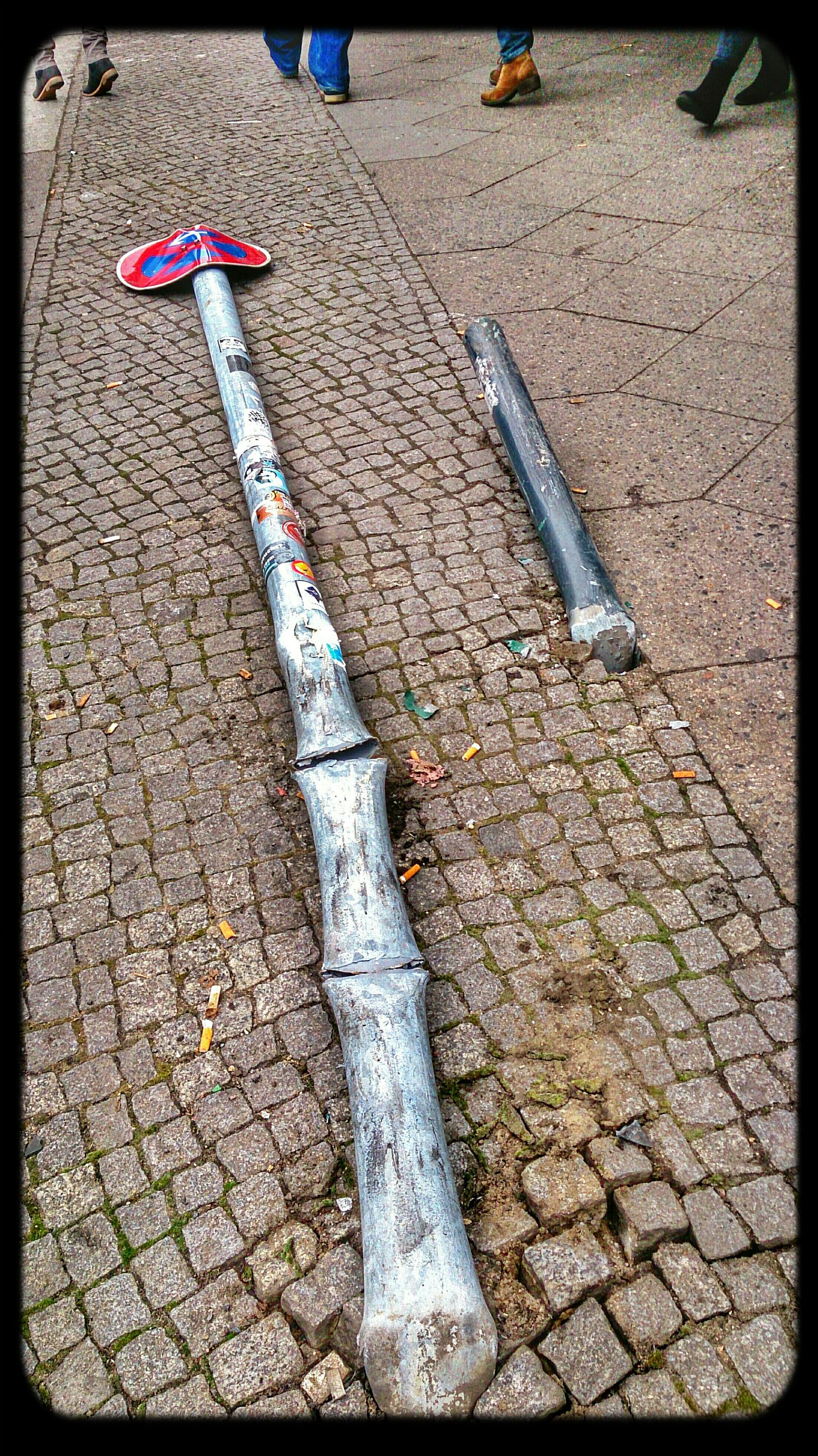 transfer print, auto post production filter, high angle view, day, street, outdoors, sunlight, red, no people, close-up, pole, shadow, metal, guidance, sidewalk, ground, still life, road, safety, cobblestone