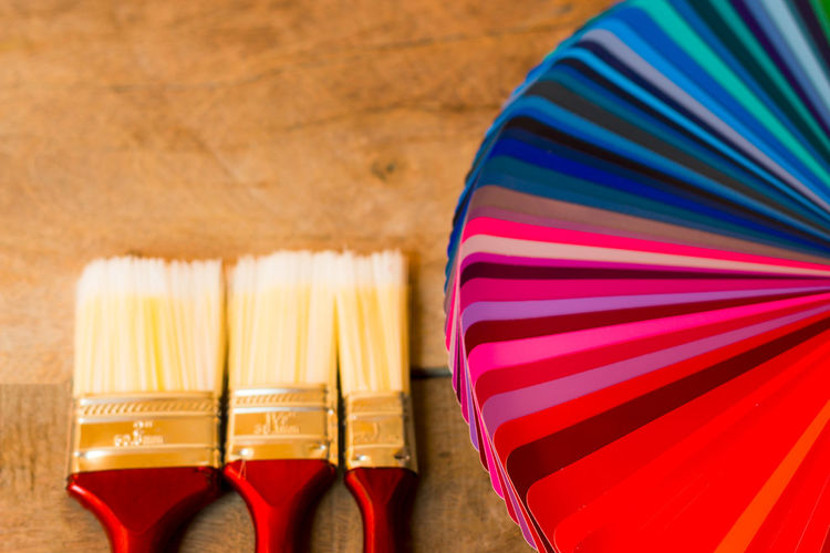 Close-up of colorful color swatches and paintbrush on table
