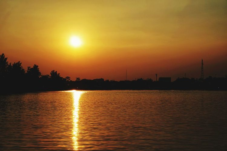 The sun is turning orange. Sunset Outdoors Silhouette Cloud - Sky Travel Destinations Tranquil Scene Lake Orange Color Sky Nature Sunlight Reflection Sun Gold Colored Water Tranquility Illuminated Scenics No People Beauty In Nature