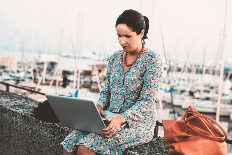 Adult woman working outdoor with a laptop oh her legs Casual Clothing Technology Wireless Technology Real People Connection One Person Sitting Water Outdoors Internet Holding Laptop Computer Using Laptop Harbor Working Worker Indipendent Woman Communication Three Quarter Length Day Legs Sea Summer