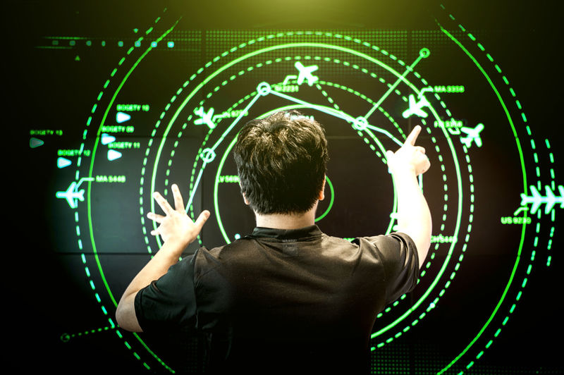 Rear view of man navigating air traffic