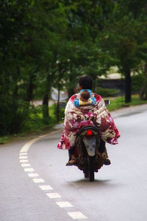 father and his child driving a road in the doi inthanon national park near Chiang Mai in northern Thailand Adult ASIA Asian  Baby Baby Carrier Childhood Cultures Dance Day Father Fatherhood  Motorcycle Nature Outdoors People Person Rear View Road Thai Thailand Traditional Clothing Tranquility Tree Vertical Wrap