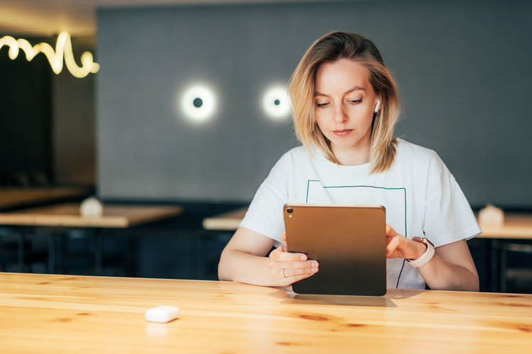 Portrait of woman holding smart phone on table