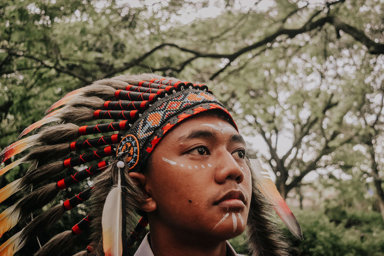 Close-up of young man wearing headdress looking away