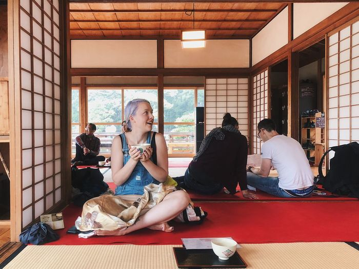 Smiling Young Woman With Tea Cup Sitting In Japanese Restaurant