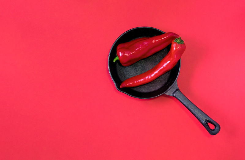 High angle view of red chili pepper against pink background