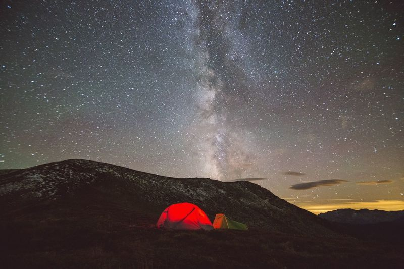 Illuminated tent on balkan mountains against constellations in sky
