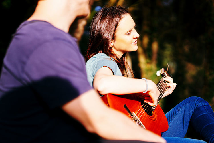 Midsection of man with woman sitting outdoors