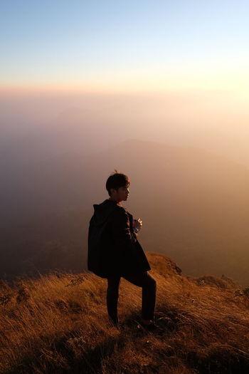 Full length of man standing on mountain against sky during sunset