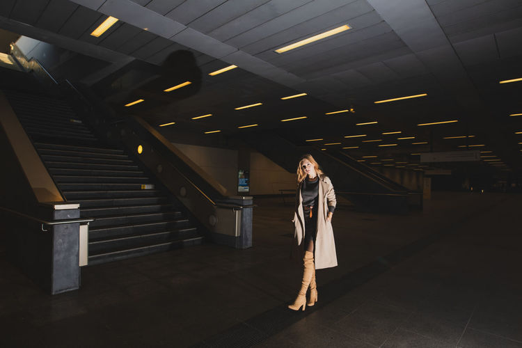 Woman Standing In Illuminated Subway