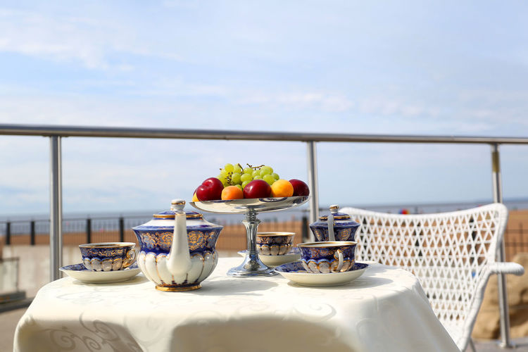 Fruits on table by sea against sky