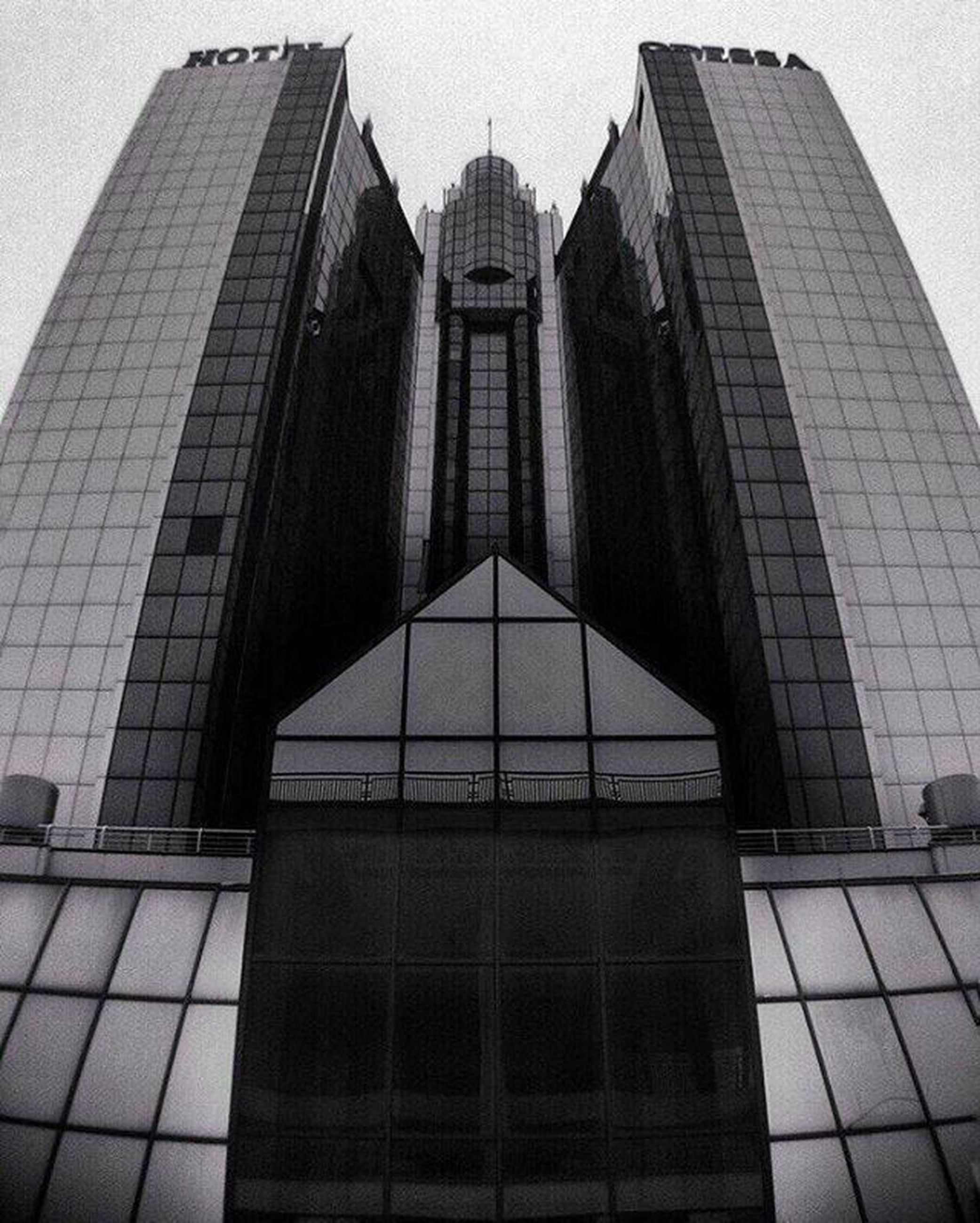 architecture, building exterior, built structure, low angle view, modern, office building, skyscraper, city, tall - high, tower, glass - material, reflection, building, clear sky, window, sky, day, no people, outdoors, city life