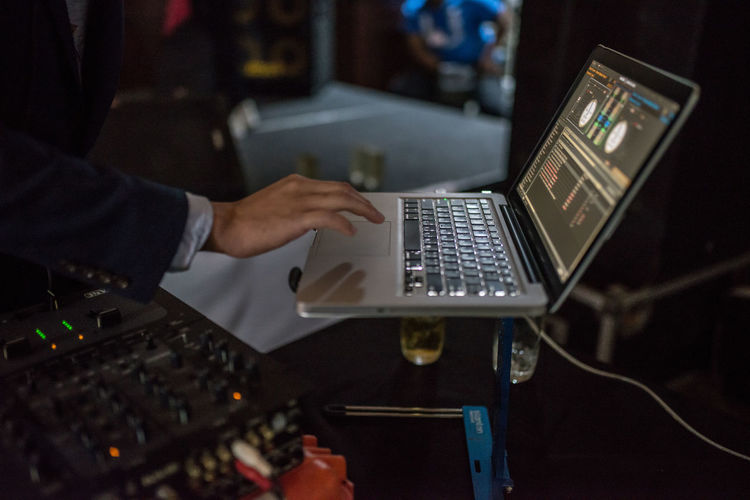 Midsection of man mixing music on laptop