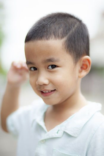 Portrait of cute smiling boy standing outdoors