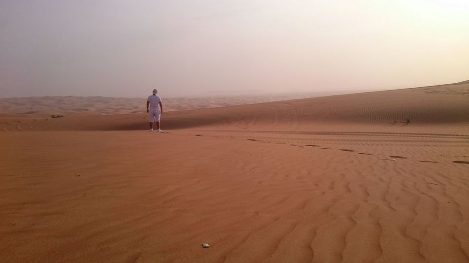 Adult Adventure Alone In The Desert Arid Climate Beauty In Nature Day Desert Footprints In The Sand Full Length Landscape Nature Outdoors People Rear View Sand Sand Dune Sky Sparse Standing Sunset Walking