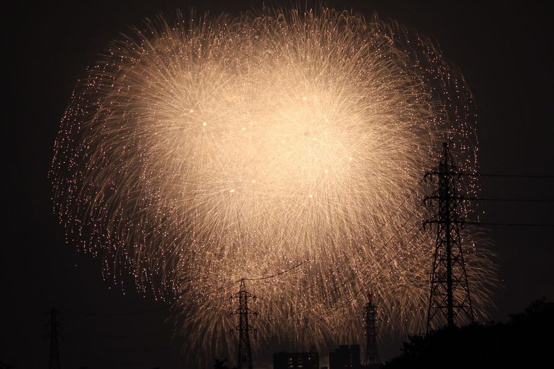 Low angle view of fireworks and electricity pylon at night
