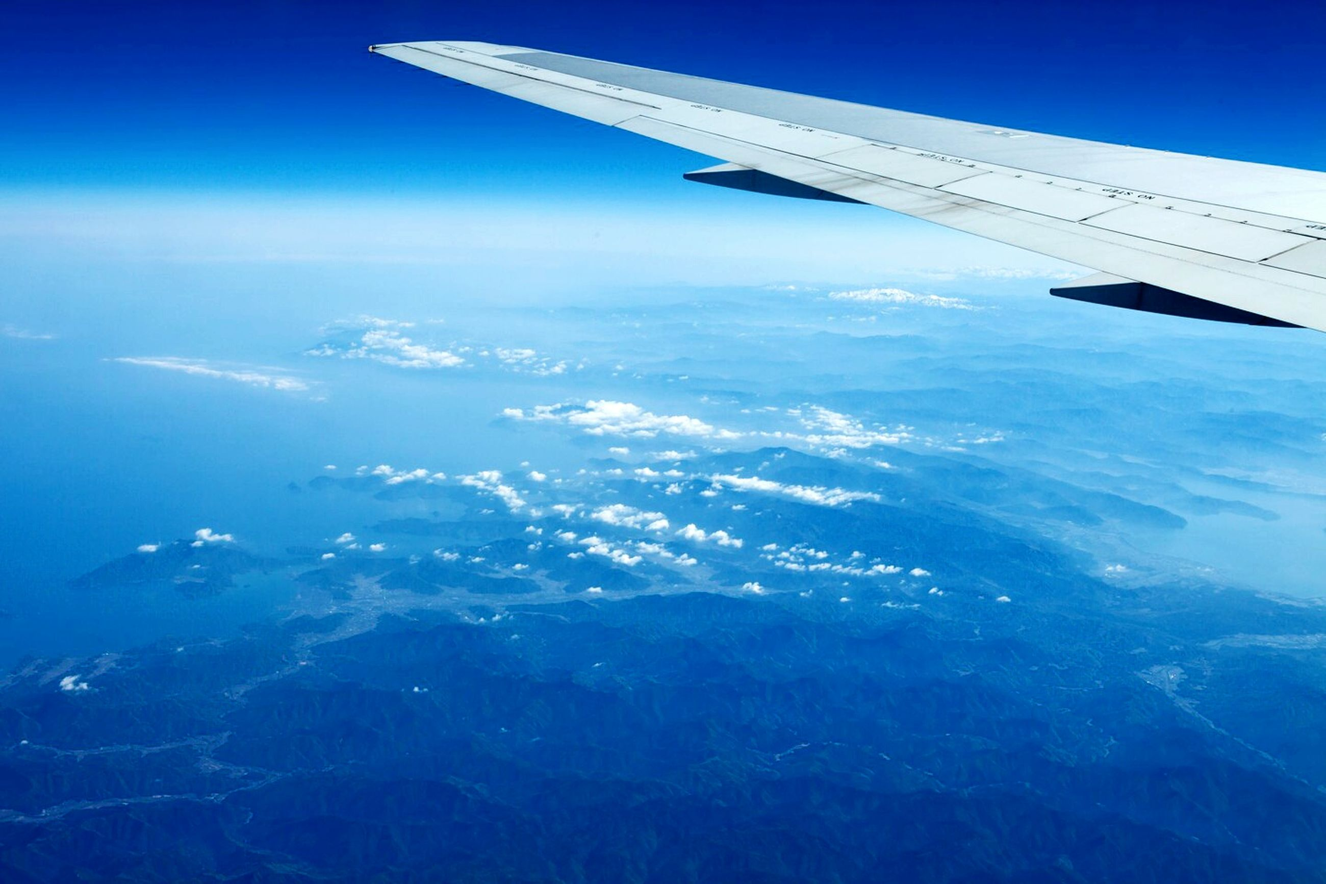 flying, airplane, air vehicle, aircraft wing, aerial view, transportation, mode of transport, mid-air, part of, blue, cropped, landscape, travel, journey, airplane wing, scenics, on the move, beauty in nature, sky, public transportation