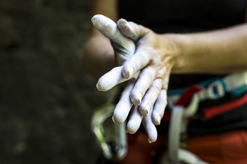 Close-Up Of Woman Rubbing Hands With Chalk
