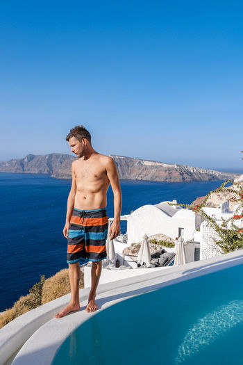 Shirtless Man Standing By Swimming Pool Over Sea Against Clear Blue Sky