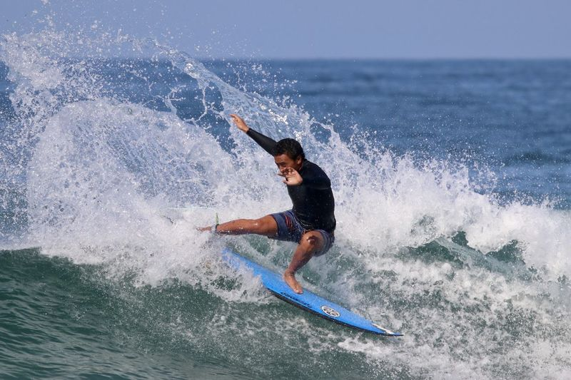 Surfer catching waves off the coast of Huntington Beach California Aquatic Forces Of Nature Man Nature Skill  Surfer Wave Editorial Use Only Extreme Sports Horizon Ocean Powerful Sky Sports Surface Level Surfboard Surfing