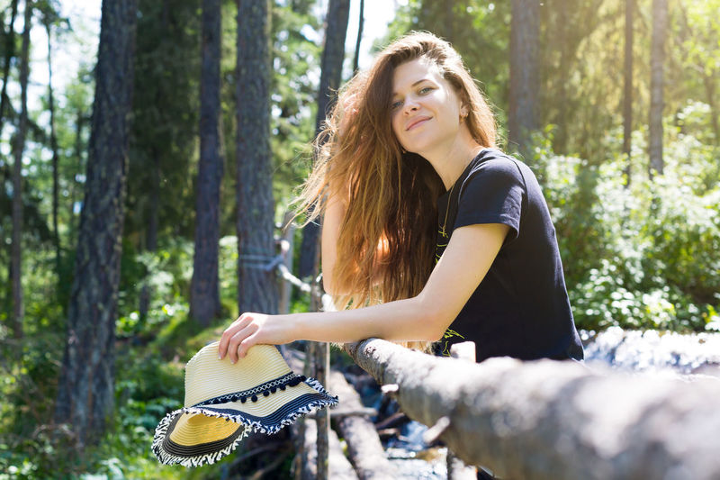 Young woman riding motorcycle in forest