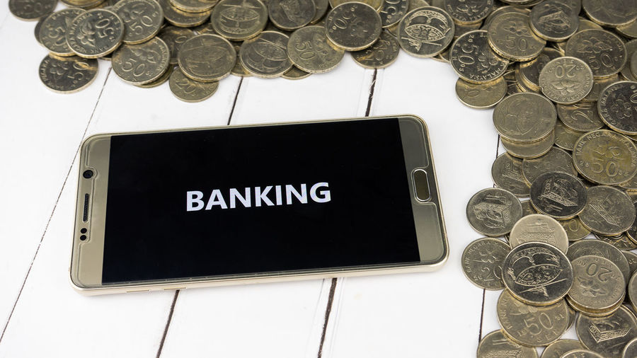 High angle view of banking text in smart phone by coins on table