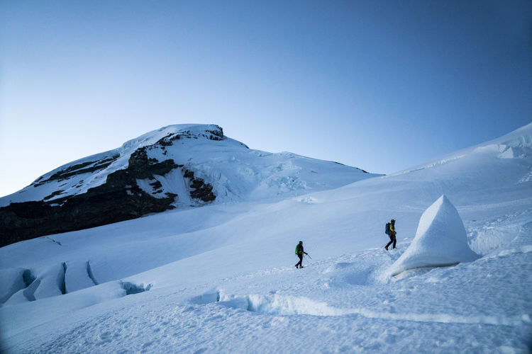 People on snowcapped mountain against clear sky
