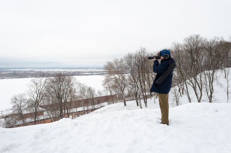 Side View Of Man Photographing On Snow Covered Landscape Against Sky