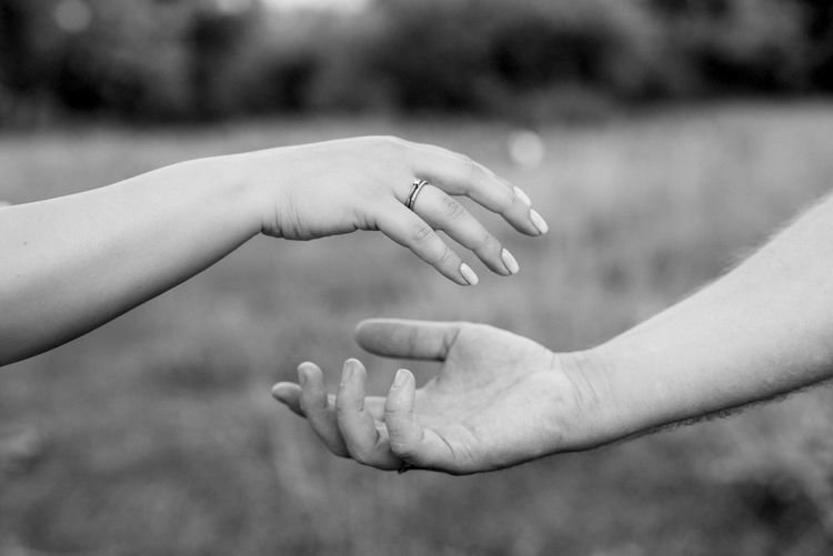 Cropped image of woman giving hand to man against blurred background