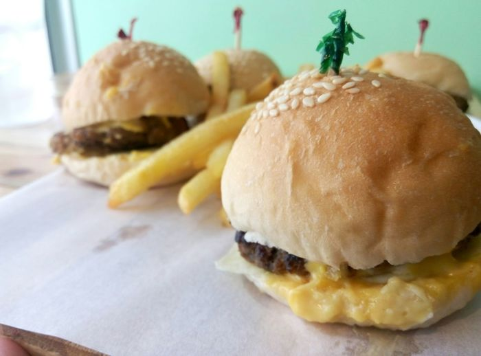 Close-up of fries with burgers on table