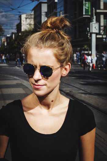 Close-Up Of Young Woman Wearing Sunglasses On Street In City