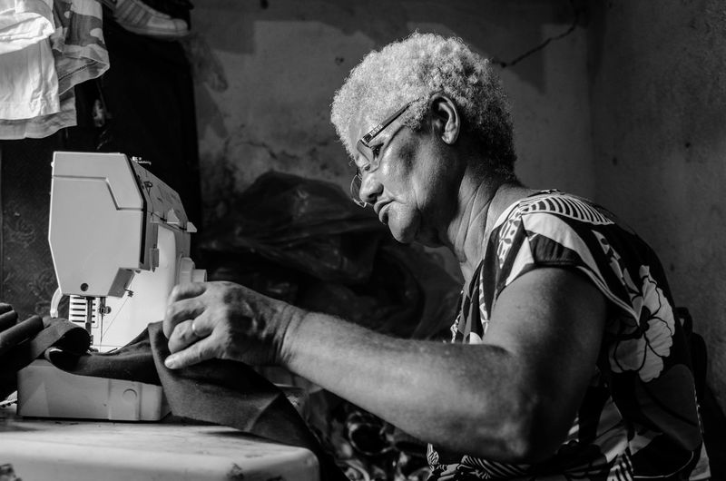 Side view of senior woman using sewing machine