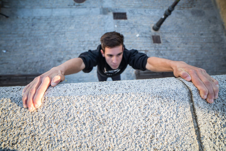 High Angle View Of Man Climbing Concrete Wall