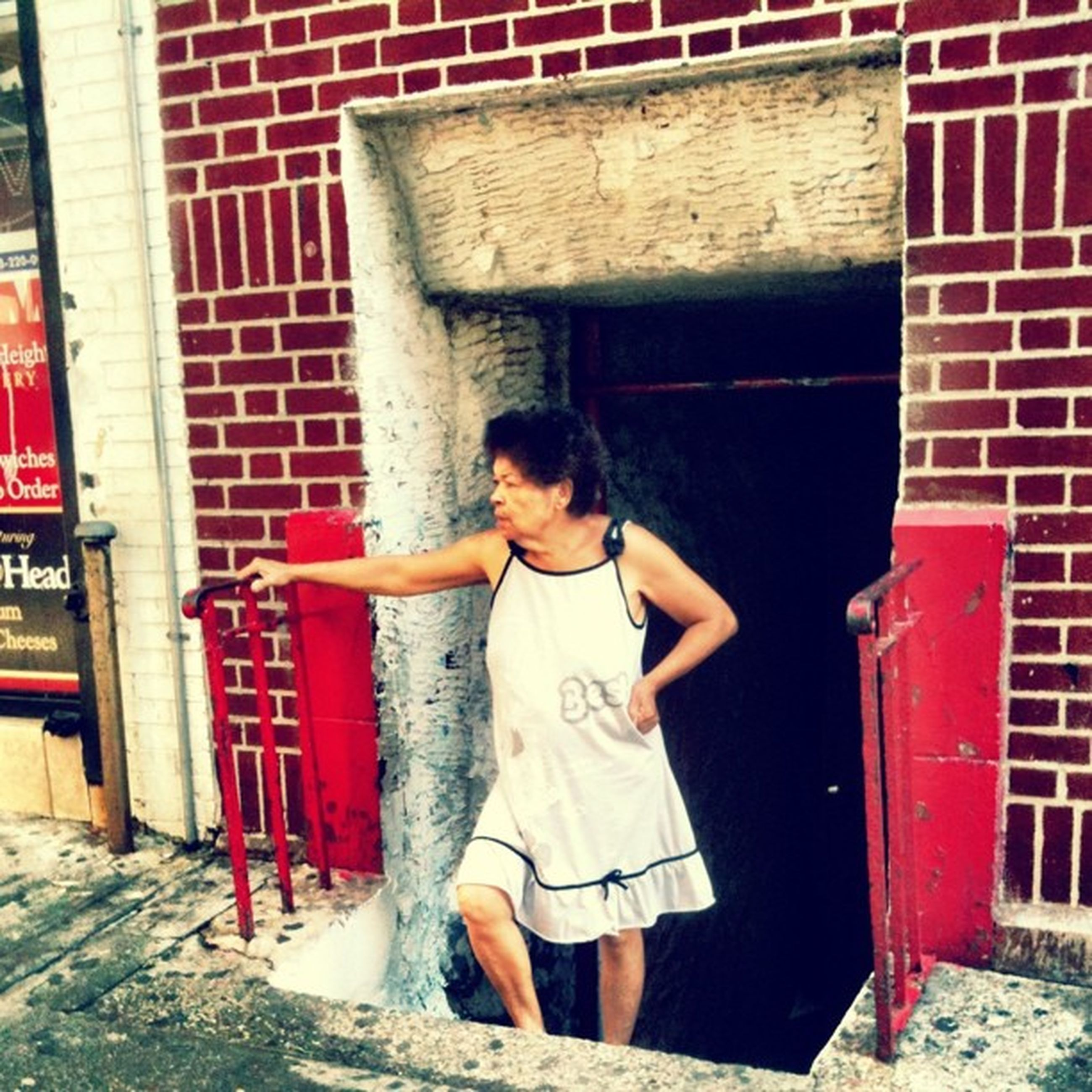 casual clothing, building exterior, lifestyles, architecture, built structure, full length, standing, leisure activity, person, three quarter length, young adult, front view, young women, red, brick wall, wall - building feature, looking at camera