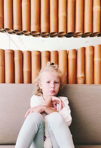 Portrait of cute girl sitting against decoration