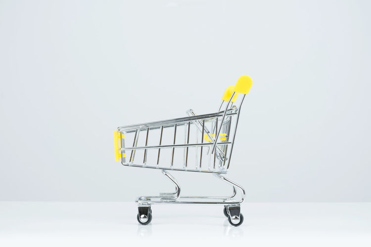 Side view of shopping cart on white Background. Basket Business Buy Commerce Consumer Consumerism Customer  E-commerce Empty Equipment Handle Industry Isolated Luggage Cart  Mall Mall Cart Market Metal Mini Object Price Purchase Push Cart Retail  Sale Shop Shopping Cart Single Single Object Small Store Super Mart Supermarket Trolley Wheel Wheels White White Background Yellow