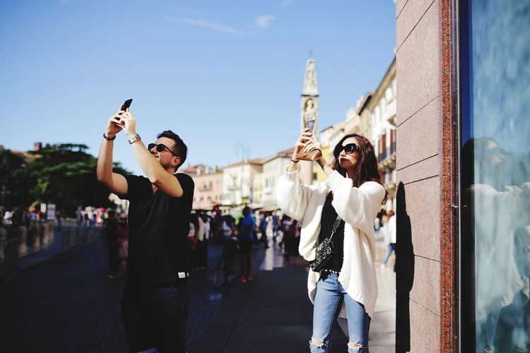 Friends photographing with smart phones while standing in city