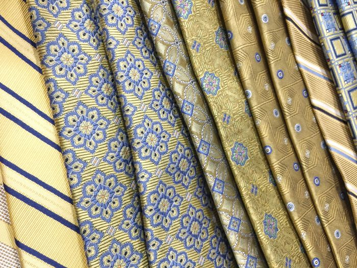 Man's tie colorful pattern background variety many dress clothes formal business attire accessory Blue yellow