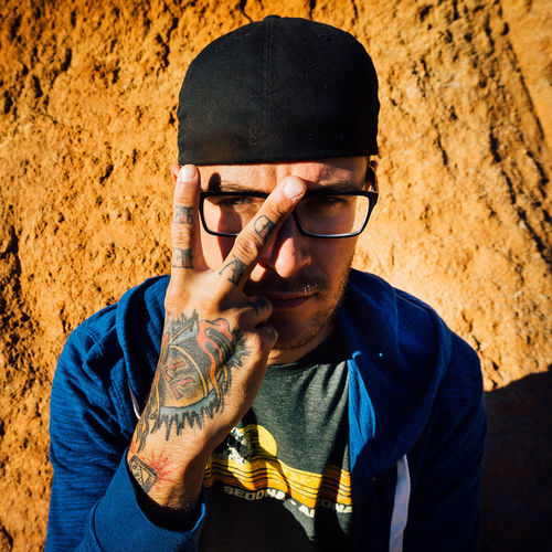 High angle view portrait of tattooed man gesturing peace sign against rock