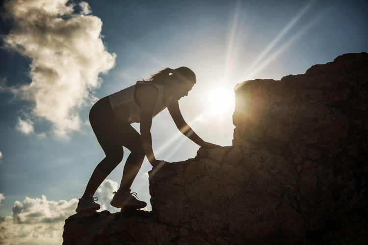 Low angle view of woman climbing on rock against sky