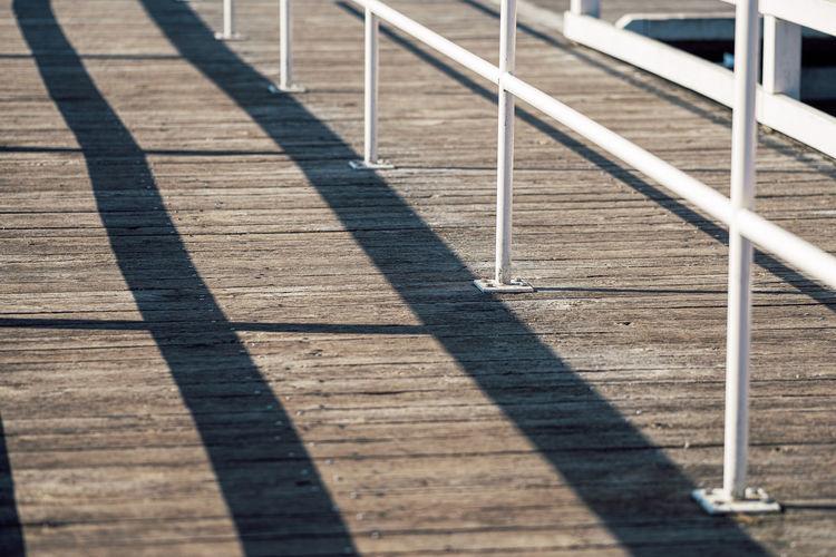 Shadow of railing on footpath