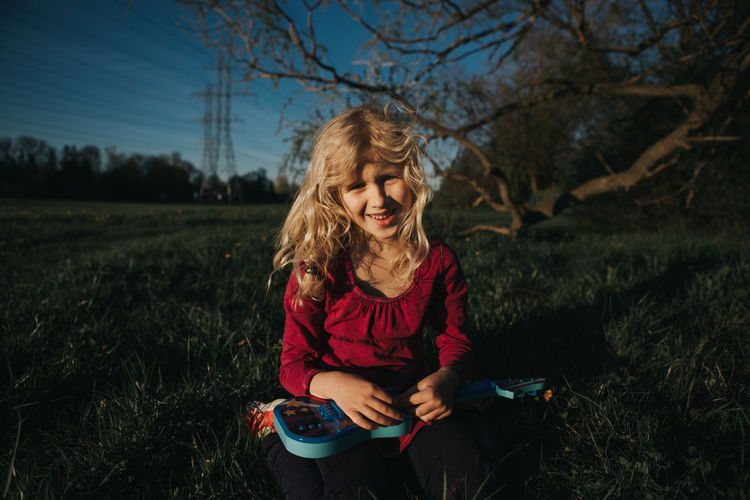 Girl playing with small guitar on field