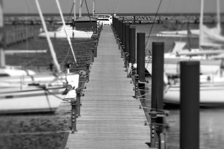 High Angle View Of Empty Pier By Boats On Sea