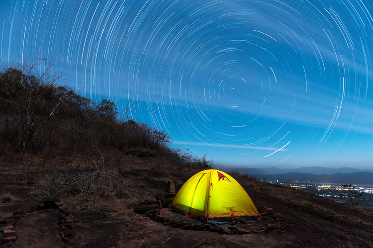 Illuminated tent on field against star field at night