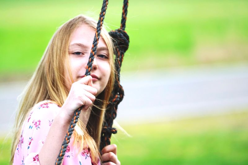 Side view portrait of girl swinging at park