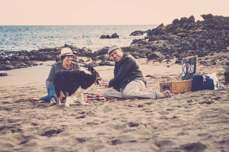 Happy Couple Sitting With Dog At Beach