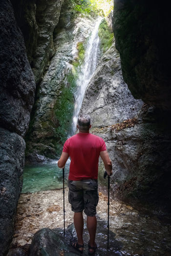 Rear view of man standing by waterfall